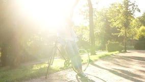 倾斜在她的自行车的可爱的女孩在城市公园 看她的色的流动,佩带的明亮桃红色和蓝色 股票录像