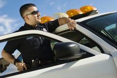 倾斜在巡逻车的警察 图库摄影