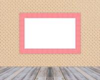 倾斜在布料墙壁和对角木地板的空白的木照片框架 库存照片