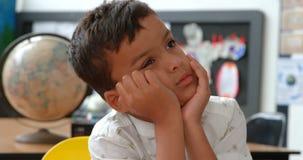 倾斜在手的体贴的亚裔男小学生正面图在书桌在教室4k 股票录像