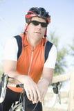 倾斜在把手的男性骑自行车者 免版税库存图片