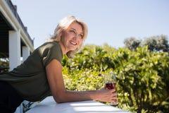 倾斜在护墙的白肤金发的妇女在餐馆 免版税库存图片
