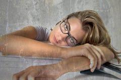 倾斜在教科书堆的可爱和美丽的疲乏的学生女孩在学习准备的检查看以后疲倦了并且乏味是 库存照片