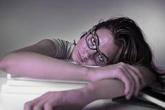 倾斜在教科书堆的年轻可爱和美丽的疲乏的学生女孩疲倦了并且用尽了学习 图库摄影