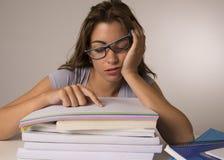 倾斜在教科书的年轻可爱和美丽的疲乏的学生女孩堆在学习以后疲倦和被用尽的睡觉 库存照片