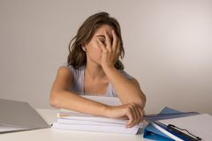 倾斜在教科书的年轻可爱和美丽的疲乏的学生女孩堆在学习以后疲倦和被用尽的睡觉 免版税库存图片