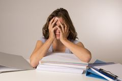 倾斜在教科书的年轻可爱和美丽的疲乏的学生女孩堆在学习以后疲倦和被用尽的睡觉 免版税库存照片