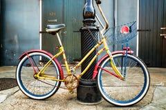 倾斜在新奥尔良路灯柱的五颜六色的葡萄酒自行车 免版税库存照片