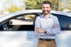 倾斜在新的汽车的确信的所有者画象 免版税库存图片
