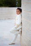 倾斜在有一只脚的墙壁的年轻人第一个圣餐男孩 库存照片