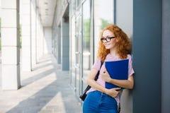 倾斜在有笔记本的墙壁的年轻微笑的红头发人学生女孩 免版税库存图片