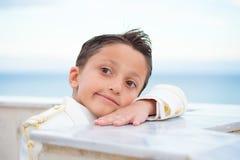 倾斜在有他的头的墙壁的年轻人第一个圣餐男孩在h 库存图片