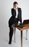 倾斜在服务台的企业夫人takling在移动电话 免版税库存照片