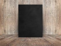 倾斜在木墙壁在木地板我的空白的黑帆布海报 免版税库存图片