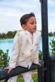 倾斜在木篱芭的年轻人第一个圣餐男孩 免版税库存图片