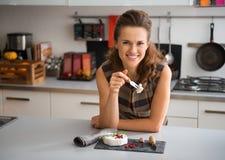 倾斜在柜台的微笑的妇女食用软制乳酪乳酪 库存图片
