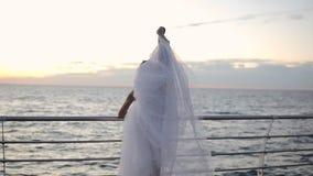 倾斜在标志横线和舒展的长的白色芭蕾舞短裙的美丽的芭蕾舞女演员 弯曲她的在垂直的麻线的腿 股票录像