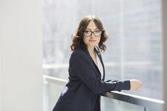 倾斜在栏杆的确信的年轻女实业家画象在办公室 免版税图库摄影