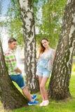 年轻倾斜在树的人和妇女在公园 免版税库存照片