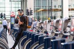 倾斜在桑坦德自行车的一个年轻人在停放站 库存图片