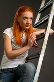倾斜在梯子的红发女孩 库存图片