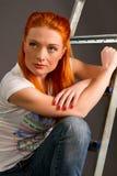 倾斜在梯子的红发女孩 库存照片