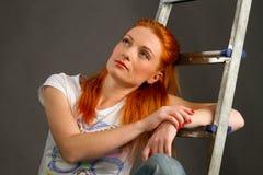 倾斜在梯子的美丽的新红发女孩 免版税图库摄影