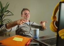 倾斜在椅子愉快指向的年轻满意和确信的商人与手指在家坐办公室的便携式计算机 免版税库存图片