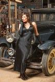 倾斜在汽车的俏丽的妇女 库存图片