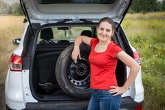 倾斜在汽车的少妇画象备用轮胎领域 图库摄影