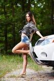 倾斜在汽车的性感的妇女 库存图片