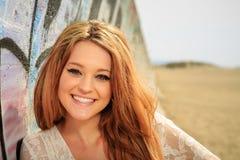 倾斜在沙子的墙壁的青少年的女孩 库存图片