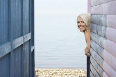 倾斜在海滨别墅外面的愉快的妇女 免版税库存图片