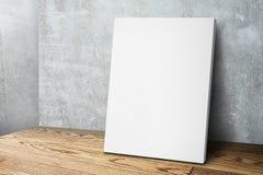 倾斜在混凝土墙和木头地板的空白的白色帆布框架 免版税库存图片
