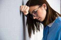 倾斜在灰色墙壁的沮丧的女实业家 库存图片