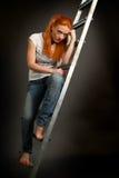 倾斜在梯子的年轻红发女孩 库存照片