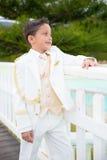 倾斜在白色木篱芭的年轻人第一个圣餐男孩 免版税库存照片