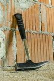 倾斜在砖墙的锤子 库存图片