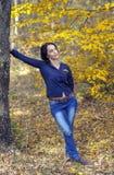 倾斜在秋天森林里的牛仔裤的女孩 库存照片