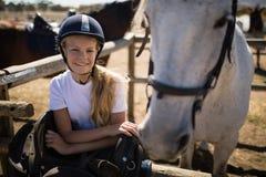倾斜在篱芭的微笑的女孩在大农场 免版税库存图片