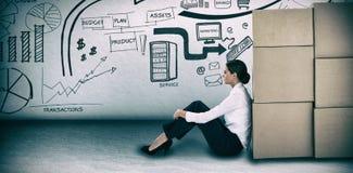 倾斜在纸板箱的女实业家的综合图象反对白色背景 库存图片