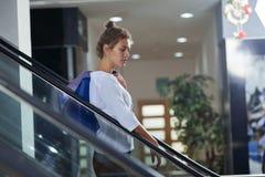 倾斜在自动扶梯扶手栏杆的端庄的妇女侧视图在购物中心 免版税库存照片