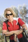 倾斜在自行车的女性骑自行车者 免版税库存照片