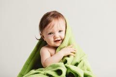 倾斜在舒适绿色毯子外面的逗人喜爱的矮小的婴孩 免版税图库摄影