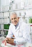 倾斜在药房的柜台的微笑的资深化学家 免版税图库摄影