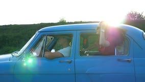 倾斜在葡萄酒车窗外面和享受旅行的太阳镜的可爱的女孩 在减速火箭的汽车的年轻夫妇旅行 股票录像