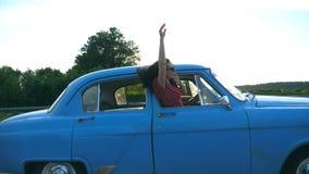倾斜在葡萄酒车窗外面和享受旅行的太阳镜的可爱的女孩 在减速火箭的汽车的年轻夫妇旅行 影视素材