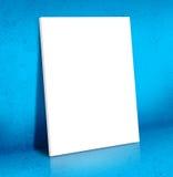倾斜在蓝色水泥室的空白的白色帆布海报,嘲笑  库存图片