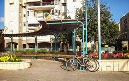 倾斜在街道半圆长凳的自行车 免版税库存照片