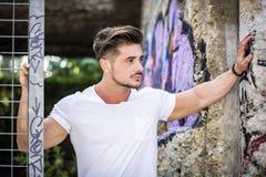 倾斜在街道画墙壁的年轻肌肉人 图库摄影